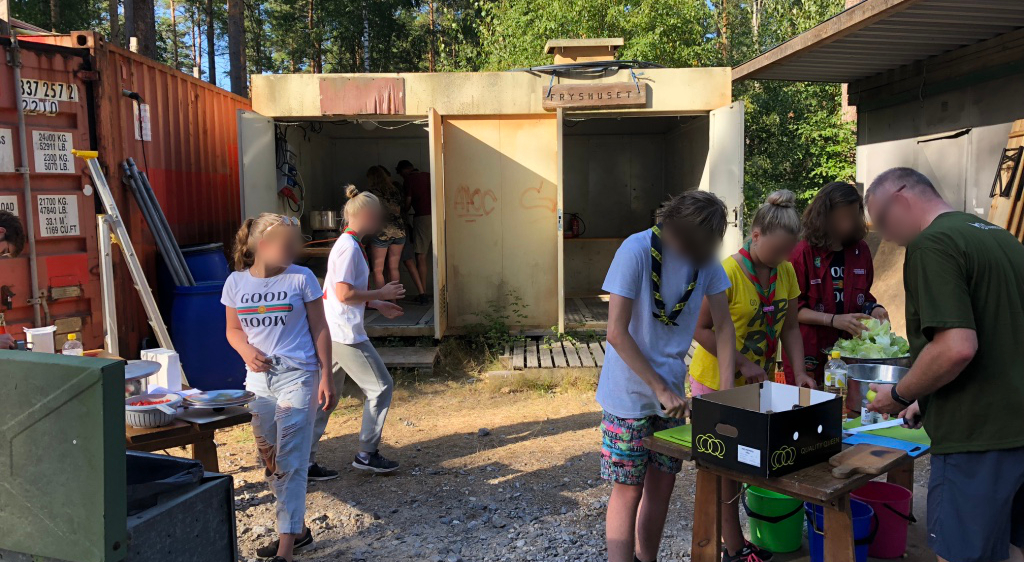 Scouts from Sweden, England and Austria work together with a Dutch leader to prepare food